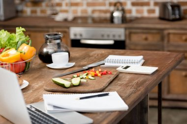 close-up shot of teleworking workplace at kitchen with food on table and laptop