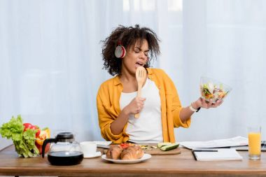 expressive young woman listening music and preparing salad at kitchen