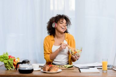 beautiful young woman listening music and preparing salad at kitchen