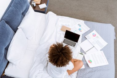 high angle view of young woman working with laptop and documents on bed