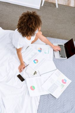 high angle view of woman working with laptop and documents on bed at home