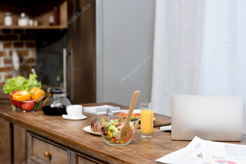Close-up shot of freelancer workplace at kitchen with food on table and laptop