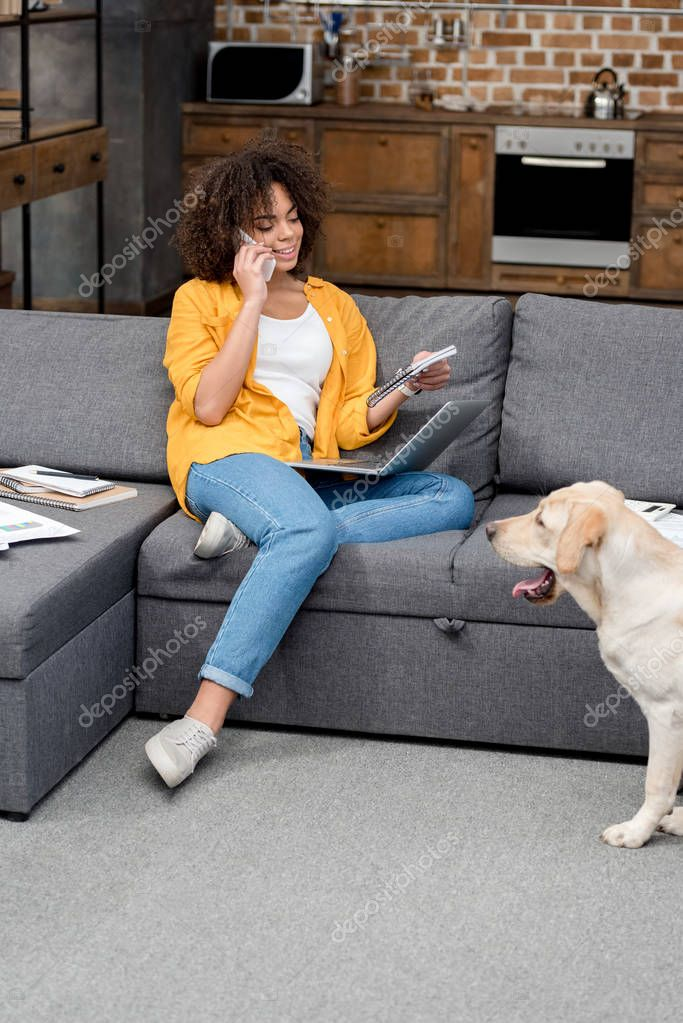 Beautiful young woman working at home and talking by phone while her dog sitting on floor