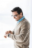 Attractive man wearing glasses checking his watch by window