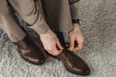 Fotografie Close-up view of man tying shoelaces of his leather shoes