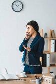 Fotografie Junge Geschäftsfrau Tisch in hellen Büro telefonieren