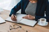 Fotografie Datailní pohled podnikatelka psaní v poznámkovém bloku na stole