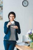 Fotografie Lächelnd Managerin genießen Kaffee während der Pause im modernen Büro
