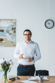 Fotografie Smiling businessman wearing glasses holding coffee cup in modern office