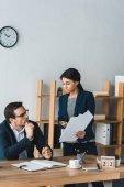 Podnikatelka, ukazující smlouvu doklady k její mužský kolega v kanceláři
