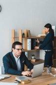 Kolegové v oblecích pracovat v moderní kanceláři