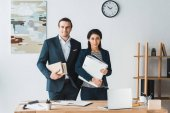 Businessman and businesswoman holding folders by working table