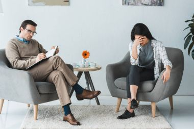 Upset african american woman in office with male psychologist