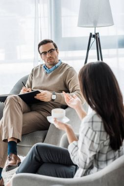 Psychologist listening to female patient talking with coffee in hands