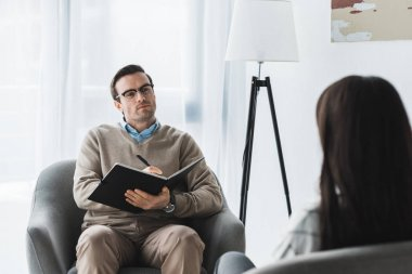 Male therapist in glasses listening to female patient in light office