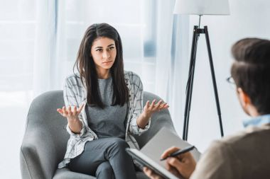 Woman complaining to male psychotherapist in doctor office