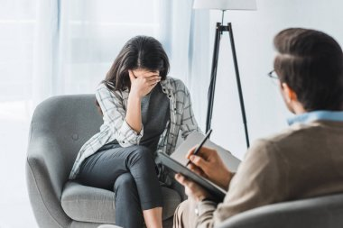 Stressed woman sitting in chair at male doctor office