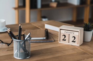 Stationery and glasses on wooden table in light office