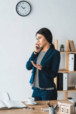Young businesswoman talking on phone by table in light office