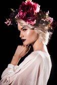 Fotografie atraktivní blondýnka s make-upem pózuje v květinový věnec, izolované na černém pozadí