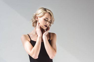 tender girl posing in elegant black dress, isolated on grey