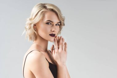 blonde young woman posing in elegant black dress, isolated on grey