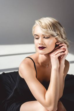 blonde smiling girl posing in elegant black dress, on grey