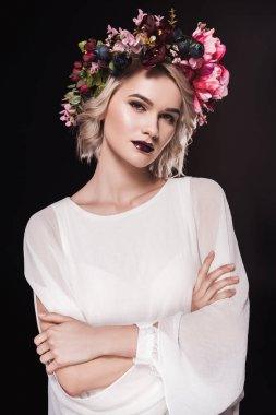 attractive blonde girl posing in white dress and floral wreath, isolated on black