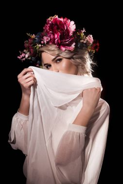 attractive tender girl posing in flower wreath with white veil, isolated on black
