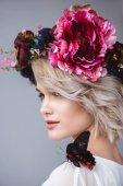 portrét elegantní dívka v květinový věnec s Krásný motýl na rameni, izolované Grey