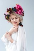 Photo attractive model posing in floral wreath with butterfly on shoulder, isolated on grey