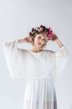 beautiful model posing in white dress and floral wreath, isolated on grey