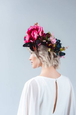 model posing in floral wreath with beautiful butterfly, isolated on grey