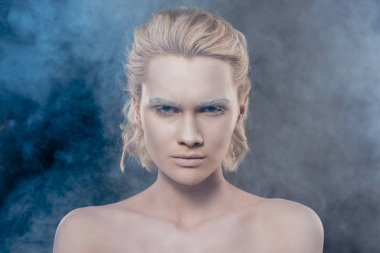 portrait of fashionable blonde girl with white makeup in smoky studio