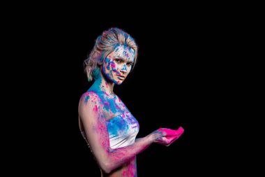 beautiful girl posing in pink and blue holi powder, isolated on black