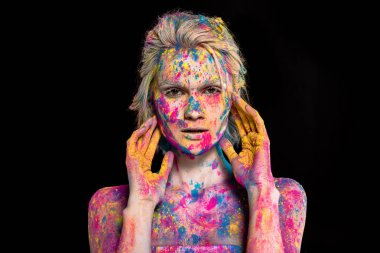 portrait of girl posing in colorful holi powder, isolated on black