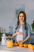 Fotografie smiling pregnant woman touching belly and looking at camera at kitchen
