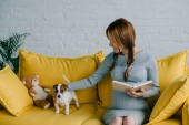 attractive pregnant woman holding book and palming with jack russell terrier in living room
