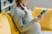 cropped image of pregnant woman looking at photos in living room