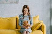 Fotografie krásná těhotná žena sedící s plyšovým medvědem v obývacím pokoji