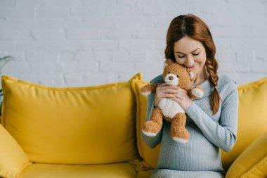 beautiful pregnant woman hugging teddy bear in living room