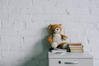 teddy bear, copybooks and books on wooden side table