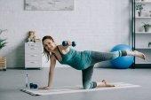Sportive těhotná žena cvičení s činkami v obývacím pokoji