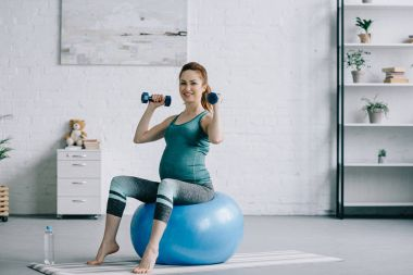 beautiful pregnant woman exercising with dumbbells on fitness ball in living room