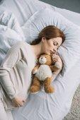 vysoký úhel pohledu atraktivní těhotná žena spí na posteli s Medvídek
