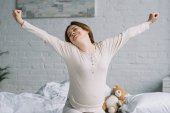 Fotografie beautiful pregnant woman stretching in bedroom in morning