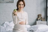Fotografie beautiful pregnant woman sitting on bed with ripe apple