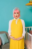 Fotografie pregnant pin up woman with pink hair touching belly in child room