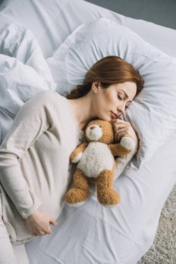 high angle view of attractive pregnant woman sleeping on bed with teddy bear