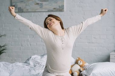 beautiful pregnant woman stretching in bedroom in morning